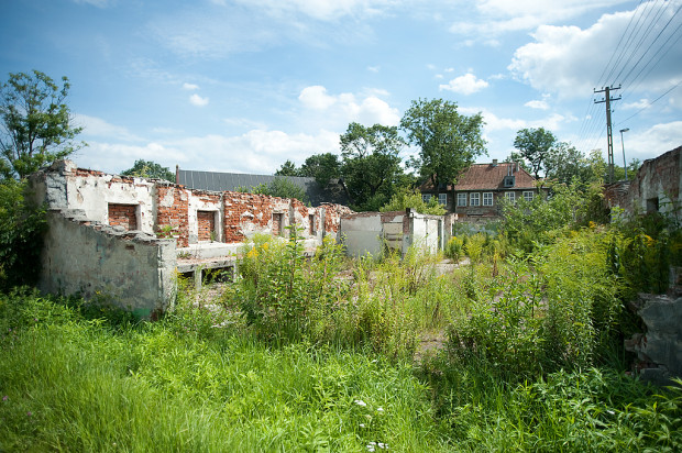 Ruiny stajni, a w tle widoczny dwór. Zdjęcie z 2012 r.