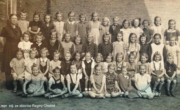 Dzieci przed szkołą na Stogach w 1943 r. W drugim rzędzie od dołu, trzecia od prawej strony siedzi Gabriela - siostra Reginy.