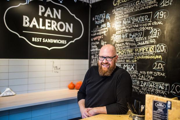 Pan Baleron podaje Philly Cheese Steak Sandwich, czyli kanapki z siekaną wołowiną, serowym sosem i przeróżnymi dodatkami.