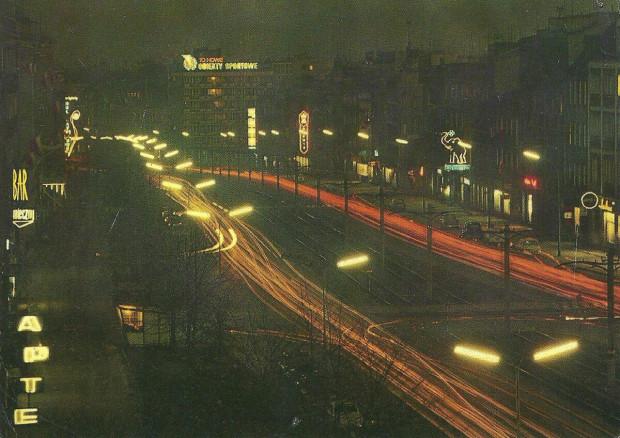 Aleja Grunwaldzka wieczorową porą, lata 60. XX wieku; widok w kierunku Śródmieścia; widoczne m.in. neony baru mlecznego, Totalizatora Sportowego i przedsiębiorstwa Chemia.