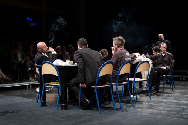 """""""Hamlet"""" Olivera Frljicia rozgrywa się przy stole, gdzie Hamlet (na krześle po prawej) sprzeciwiający się woli mającego charakter mafioza Klaudiusza (z papierosem po lewej) nie ma żadnych szans na przetrwanie."""