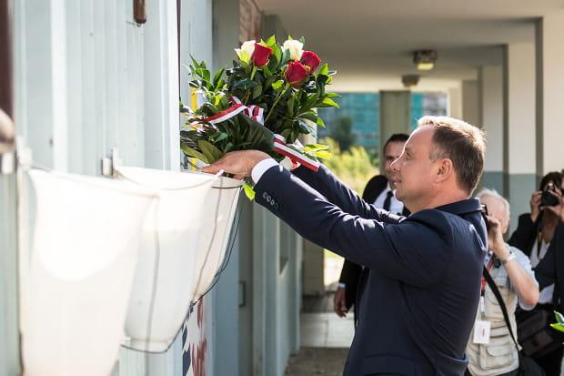 Prezydent Andrzej Duda podczas składania kwiatów przy stoczniowej bramie.