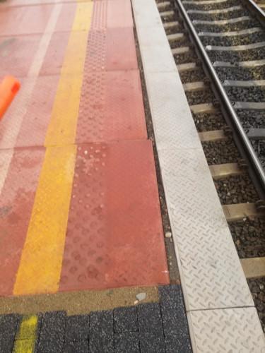 Pasażerowie zwracają uwagę na niedoróbki podczas kładzenia nowej nawierzchni peronu.