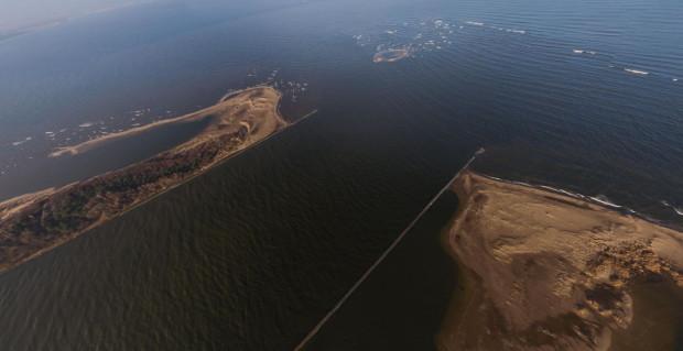 Ujście przekopu Wisły ciągle rośnie z powodu niesionego  przez rzekę piasku, co powoduje jej wypłycenie w tym rejonie. To natomiast powoduje, że wody powodziowe, kra i lód nie są w stanie dojść do zatoki i powstaje zator. Poziom wody wtedy rośnie i może po przerwaniu wałów dotrzeć aż do Gdańska, czy w drugą stronę, nawet do Elbląga.
