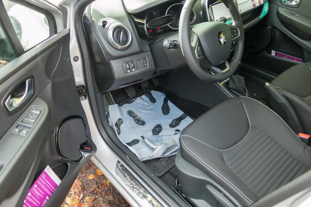 Wnętrze samochodu z folią ochroną przy fotelu kierowcy.