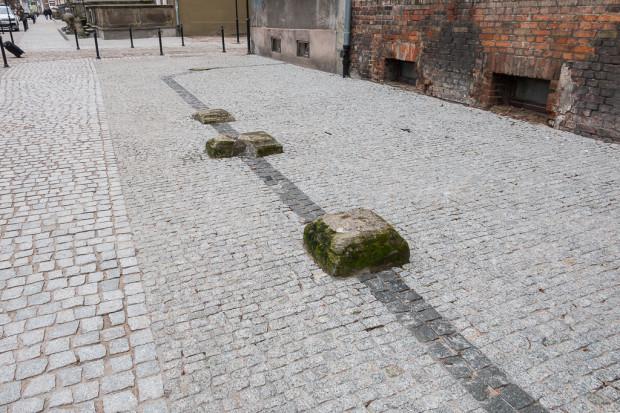 Pozostałości dawnych przedproży na środku chodnika.