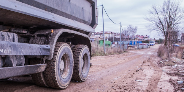 Ciężarówki wyjeżdżające z budowy zanieczyszczają błotem ulice.