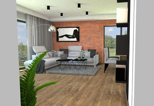 Druga koncepcja zakłada bardziej spokojną i stonowaną kolorystykę, której głównym elementem jest szara narożna sofa oraz czerwona cegła na całej ścianie łączącej pokój dzienny z kuchnią.