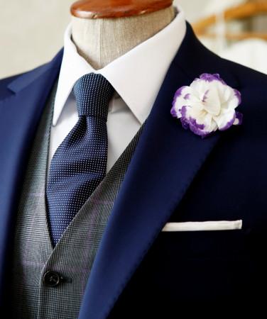 Krawat lub mucha z jedwabiu jednolitego lub w drobny wzór, biała lniana poszetka złożona po prezydencku, czarne półbuty ze skóry licowej to elementy, które skutecznie podniosą oficjalność naszego stroju.