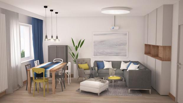 W tym przypadku szarość oraz biel, zgodnie z potrzebami właścicieli, zostały wzbogacone żółtymi oraz niebieskimi akcentami, które ożywiają wnętrze.
