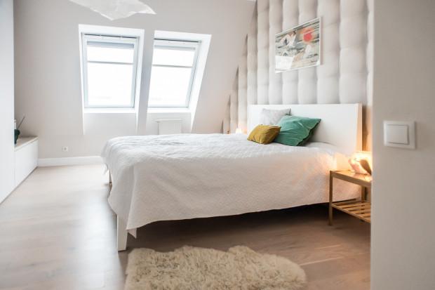 Aranżacja sypialni została zachowana w bieli. Ciekawym akcentem nawiązującym do Mid Century Modern jest okładzina ścienna.