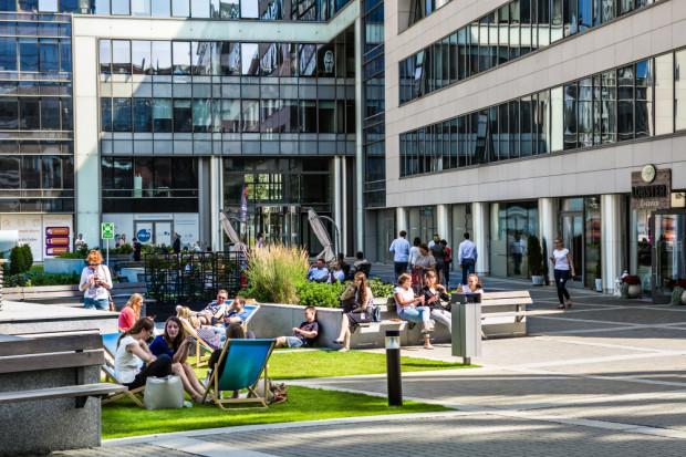 Wewnętrzny dziedziniec w Olivia Business Centre w ciągu dnia zapełniony jest ludźmi.