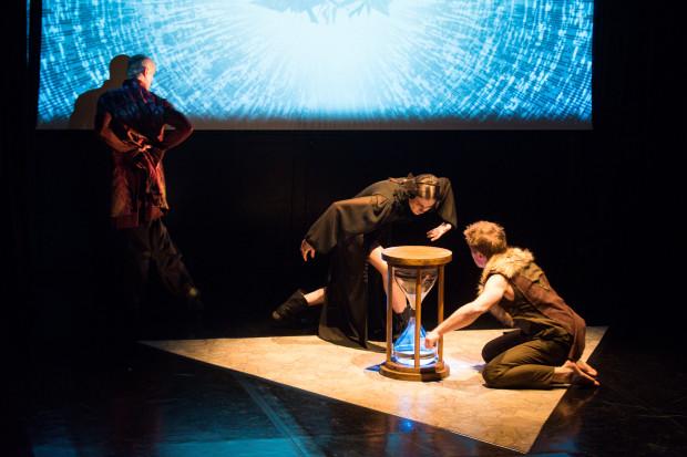 """Minimalistyczna scenografia """"Melencolii"""" składa się z dużego ekranu projekcyjnego w tle, jasnego trójkąta na podłodze i  wielkiej klepsydry, budzącej zainteresowanie postaci na scenie i podziw na widowni."""