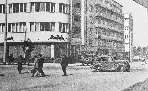 Samochody przed gmachem Zakładu Ubezpieczeń Społecznych i kawiarnią Bałtyk.