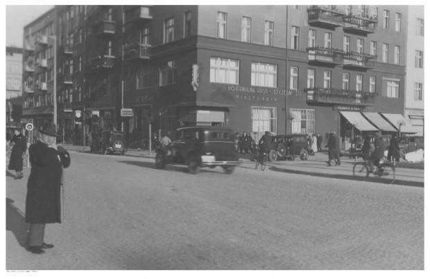 Samochody i rowery na ulicy Świętojańskiej. Widoczny budynek Komunalnej Kasy Oszczędności i kawiarni Bons Amis.