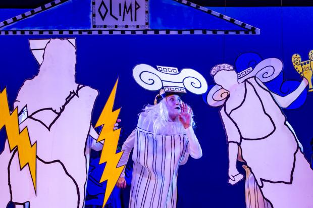 Greccy bogowie przedstawieni zostali za pomocą tekturowych makiet sylwetek z kojarzonymi (przeważnie) z nimi atrybutami - Zeus (po lewej) dzierży pioruny, a Hera (po prawej), dostała do ręki kielich z ambrozją.
