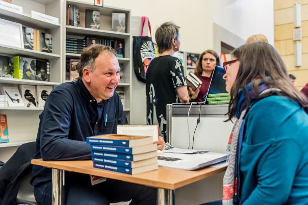 Cezary Łazarewicz podpisuje książki podczas Gdańskich Targów Książki w 2018 roku.