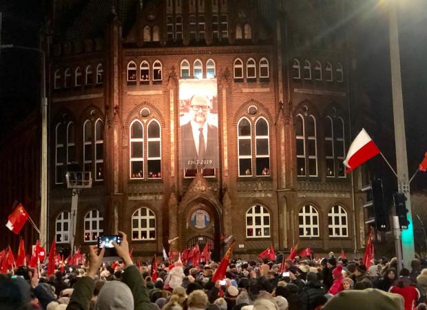 Prezydenta Gdańska żegnają tysiące mieszkańców, którzy przynieśli flagi Gdańska i Polski, kwiaty, znicze i elektryczne świeczki.