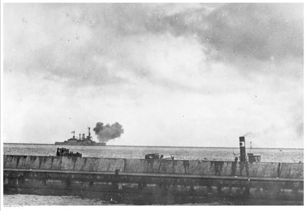 """Niemiecki pancernik """"Schlesien"""" ostrzeliwuje 27 września 1939 r. polskie umocnienia na Helu. Na pierwszym planie falochron portu w Gdyni."""