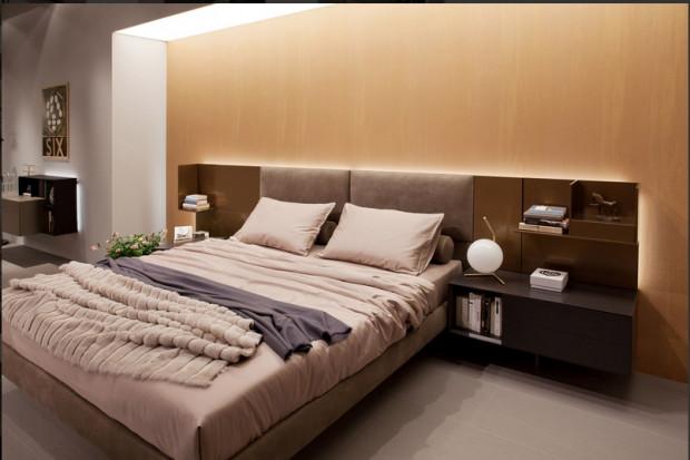 Jeśli użyjemy odpowiedniej palety barw, podkreślenie kolorem jednej ściany we wnętrzu sypialni będzie tworzyć atmosferę relaksu i odprężenia. W tej aranżacji łagodne pastelowe odcienie połączono z  tapetą strukturą przypominającą tkaninę. Bursztynowy odcień ma właściwości uspokajające i rozświetlające.