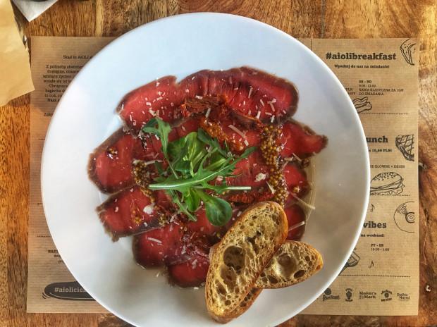 Wołowe carpaccio z suszonymi pomidorami, rukolą, parmezanem, oliwą z musztardy francuskiej i pieczywem korzennym w Aioli.