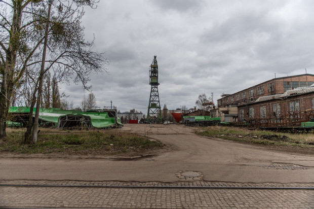 Przestrzeń, gdzie stanie wioska kontenerowa sąsiaduje z zabytkowymi halami stoczni, dźwigiem M3 i nabrzeżem.
