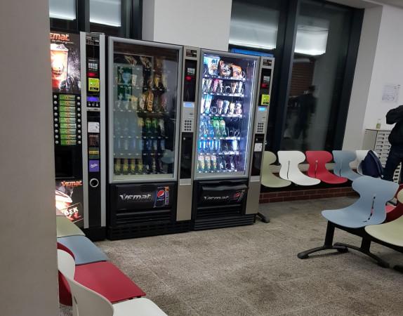W holu przed wejściem do basenowej szatni stoją automaty ze słodyczami i gazowanymi napojami.