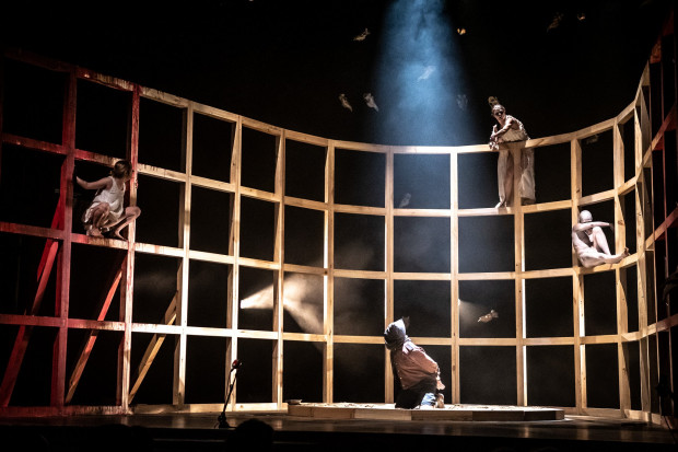 Na scenie dominuje drewniana konstrukcja, przypominająca klatkę i szkielet statku, po którym poruszają się bohaterowie.