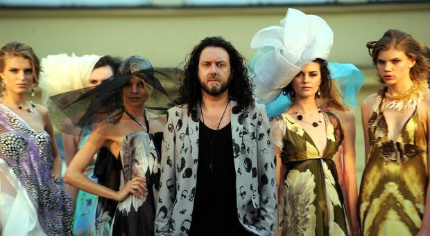 Michał Starost z modelkami po pokazie w ogrodzie hotelu Grand.