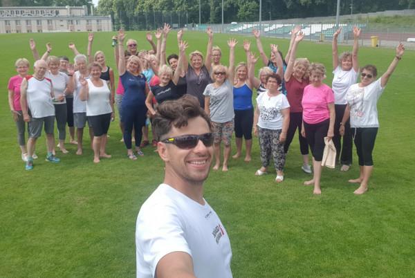 Łukasz Marszałkowski wraz z grupą seniorów, z którymi odbywa zajęcia gimnastyczne