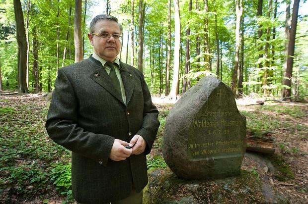 Leśniczy z Sopotu Waldemar Baranowski przy kamieniu upamiętniającym zbrodnię na jego koledze po fachu.