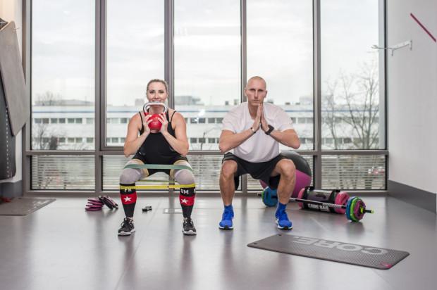 Trening w sali fitness to świetna zabawa, niezależnie od tego, czy ćwiczymy z akcesoriami, czy tylko z własnym ciężarem ciała. Przykładowe ćwiczenia na wiele grup mięśni prezentują Katarzyna i Igor Janikowie.