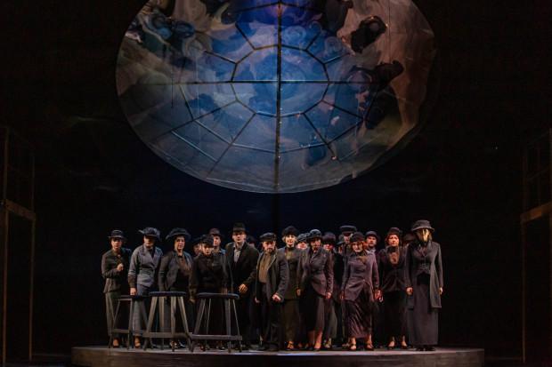 """W ciekawej scenografii Hanny Wójcikowskiej-Szymczak główną rolę odgrywa umieszczona centralnie scena obrotowa i przypominające kulę ziemską, wiszące nad nią lustro, odbijające """"w krzywym zwierciadle"""" wszystkie działania sceniczne."""