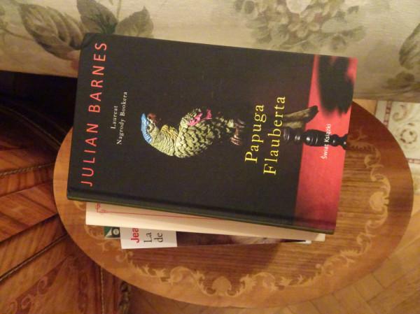 """Na szczycie stosiku Moniki Milewskiej przysiadła niedawno wznowiona """"Papuga Flauberta"""". Pod książkami chybotliwy stolik z pozytywką."""