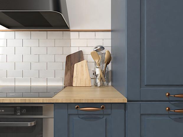 Koncepcja pierwsza. Białe kafelki i dębowe drewno równoważą ciemne fronty kuchni. Miedziane akcenty dodają wnętrzu charakteru.
