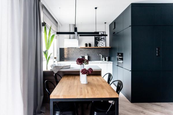 Jasna część kuchni stanowi przeciwwagę dla czarnej zabudowy meblowej oraz strefy dziennej.