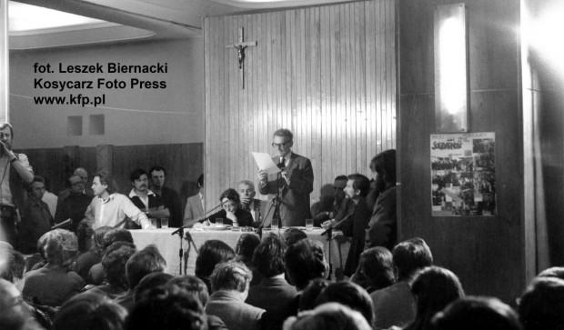 """Lech Bądkowski przemawia na pierwszym, ogólnopolskim zebraniu przedstawicieli formującego się Niezależnego Samorządnego Związku Zawodowego we Wrzeszczu. Właśnie wtedy zapadła decyzja o nadaniu organizacji nazwy """"Solidarność"""". Na lewo od Bądkowskiego siedzi Joanna Gwiazda, po prawej Lech Wałęsa."""