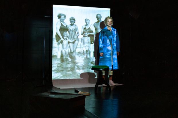 W tle, za plecami aktorki, oglądać można zapętlone archiwalne zdjęcia poetki.