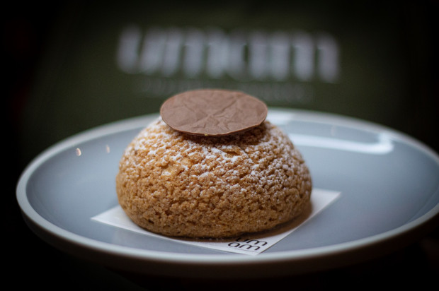 Cukiernia UMAM przygotowała nietypową wersję pączka: ciasto parzone nadziane waniliowym budyniem i karmelowym musem oraz kremem z mango. Na wierzchu ozdobiony czekoladą.