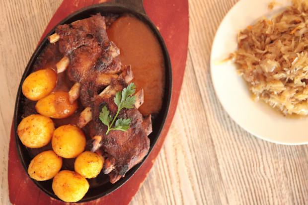 Pieczone żeberka w sosie barbecue, podane z pieczonymi ziemniakami i kiszoną kapustą zasmażaną.
