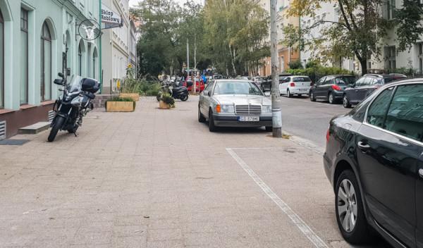 Tego typu parkowanie jest niezgodne z przepisami i zasadami panującymi w strefie płatnego parkowania. Motocyklista powinien zająć miejsce na chodniku tuż przy jezdni, pomiędzy autami.