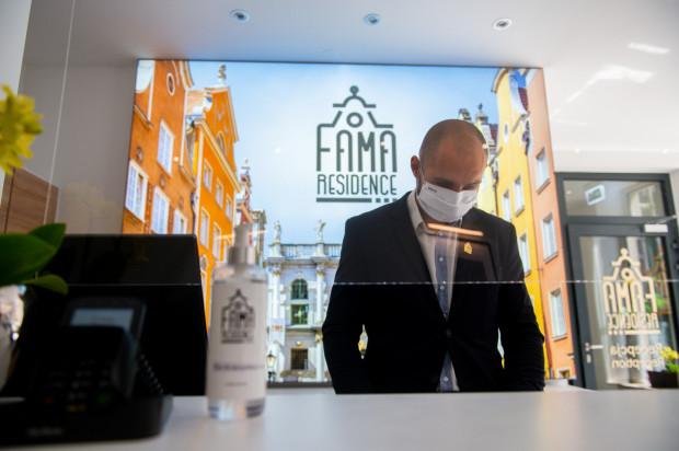 Maseczka, rękawiczki, środki do dezynfekcji i szyba z pleksi w recepcji - tak wyglądają przygotowania do przyjęcia gości w hotelu Fama Residence w Gdańsku.