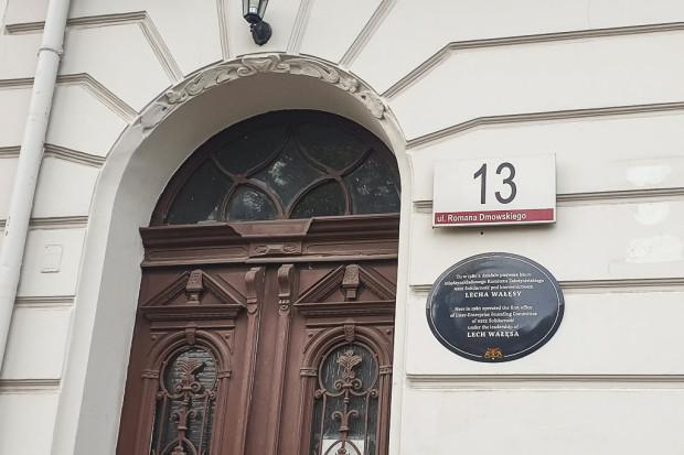 """Tablica z numerem budynku przy ul. Dmowskiego wraz z informacją na temat życiorysu Lecha Wałęsy (pod tym adresem działało pierwsze biuro """"Solidarności"""")."""