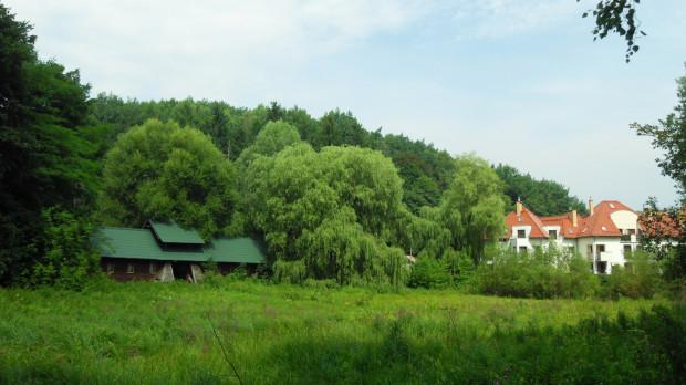 Widok na łąkę przed bramą harcerskiego obozowiska (nakryta zielonym dachem), na której zostanie wybudowany zbiornik.