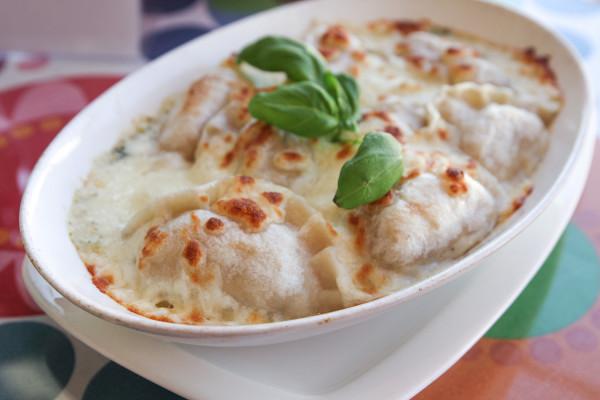 Pierogi zapiekane z mozzarellą (8 szt.): ruskie w sosie serowo-brokułowym.