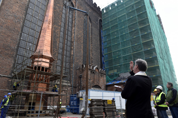 Montaż ostatniej sygnaturki na dachu bazyliki Mariackiej w Gdańsku po prawej stronie widoczny ks. proboszcz Ireneusz Bradtke. Fotografia pochodzi z 28 kwietnia 2018 r.
