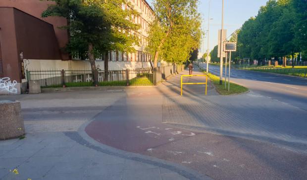 Przejazd rowerowy przez ul. Piramowicza, na którym panuje ograniczona wzajemna widoczność, a ponadto rowerzyści muszą jeszcze uważać na barierkę ustawioną przy ciasnym i wąskim łuku.