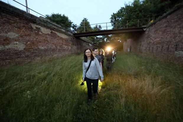 Podczas odkrywania niedostępnych za dnia zakamarków starej twierdzy przewodnik w historycznym mundurze wprowadza w burzliwe dzieje tego wyjątkowego miejsca. Być może w dawnych fortyfikacjach kryją się nie tylko nietoperze...
