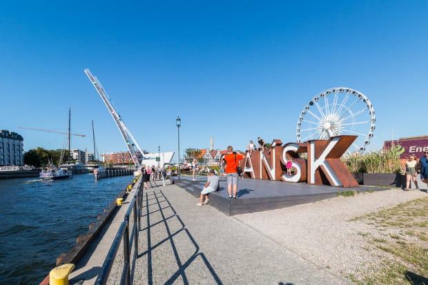 """Drugie życie Ołowianki dało otwarcie kładki dla pieszych. Atrakcyjność tego miejsca wzrosła też, gdy stanęło tam koło widokowe i napis """"Gdańsk""""."""