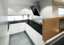 Białe lakierowane fronty połączone z czarnymi, grafitowymi blatami pozwalają utrzymać pomieszczenie w jasnej tonacji, a jednocześnie wpływają na zdecydowany charakter wnętrza.